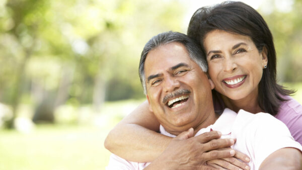 Senior couple smiling and posing in a park